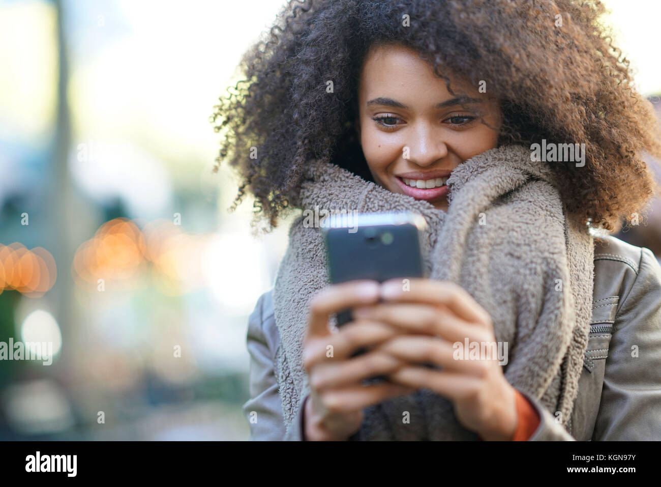 Girl sitting at Bryant park, sending message with smartphone - Stock Image
