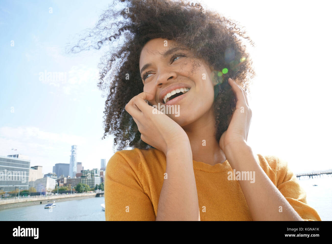 Cheerful mixed raced girl in Manhattan talking on phone - Stock Image
