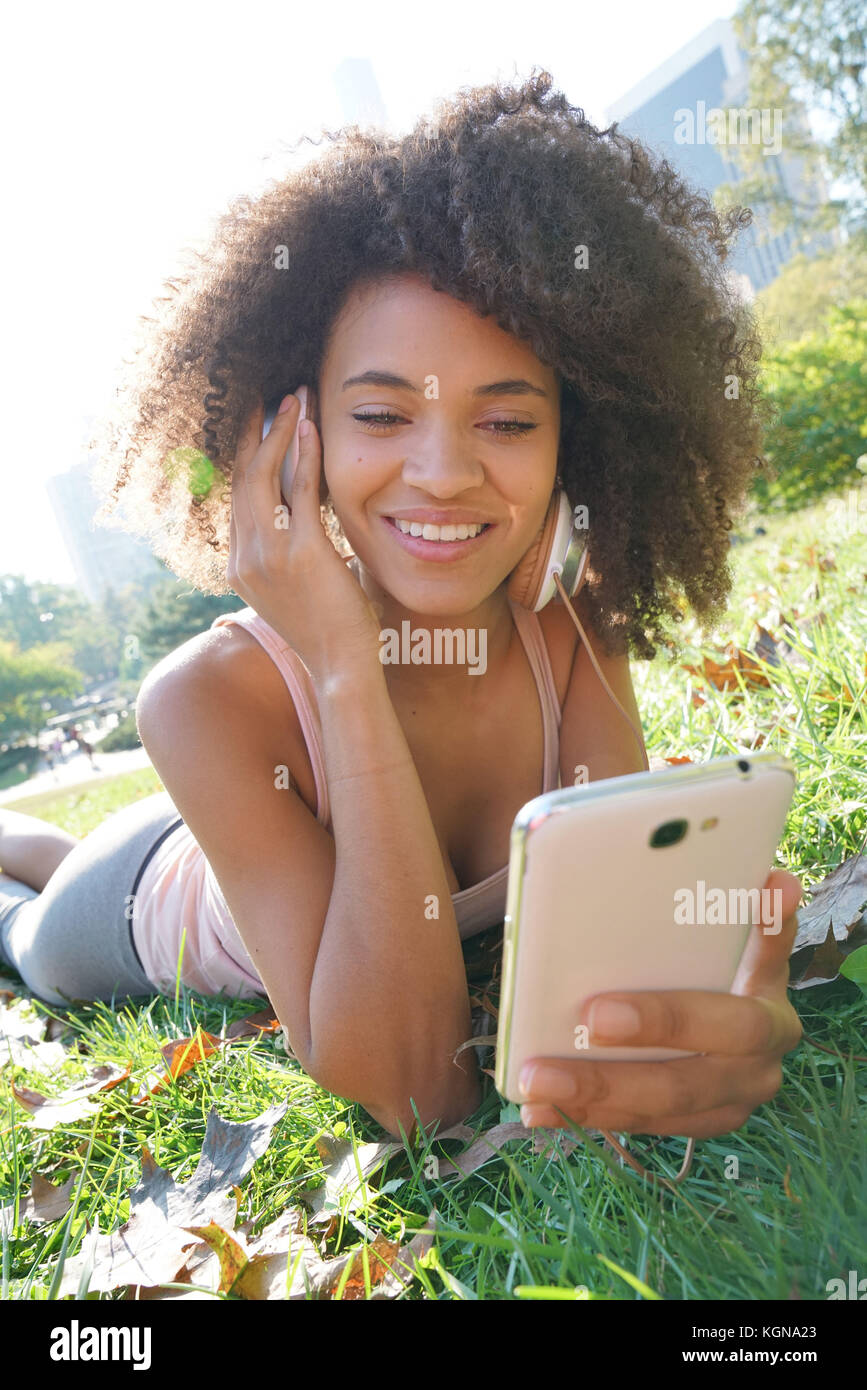 Beautiful fitness girl relaxing at Central park with headset on - Stock Image