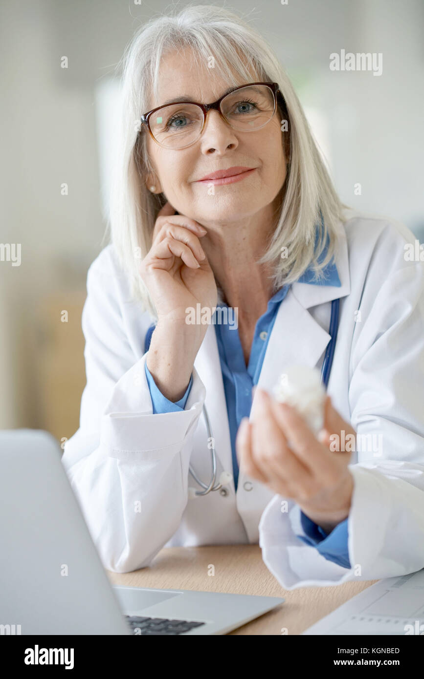 Senior female doctor giving prescription to patient - Stock Image
