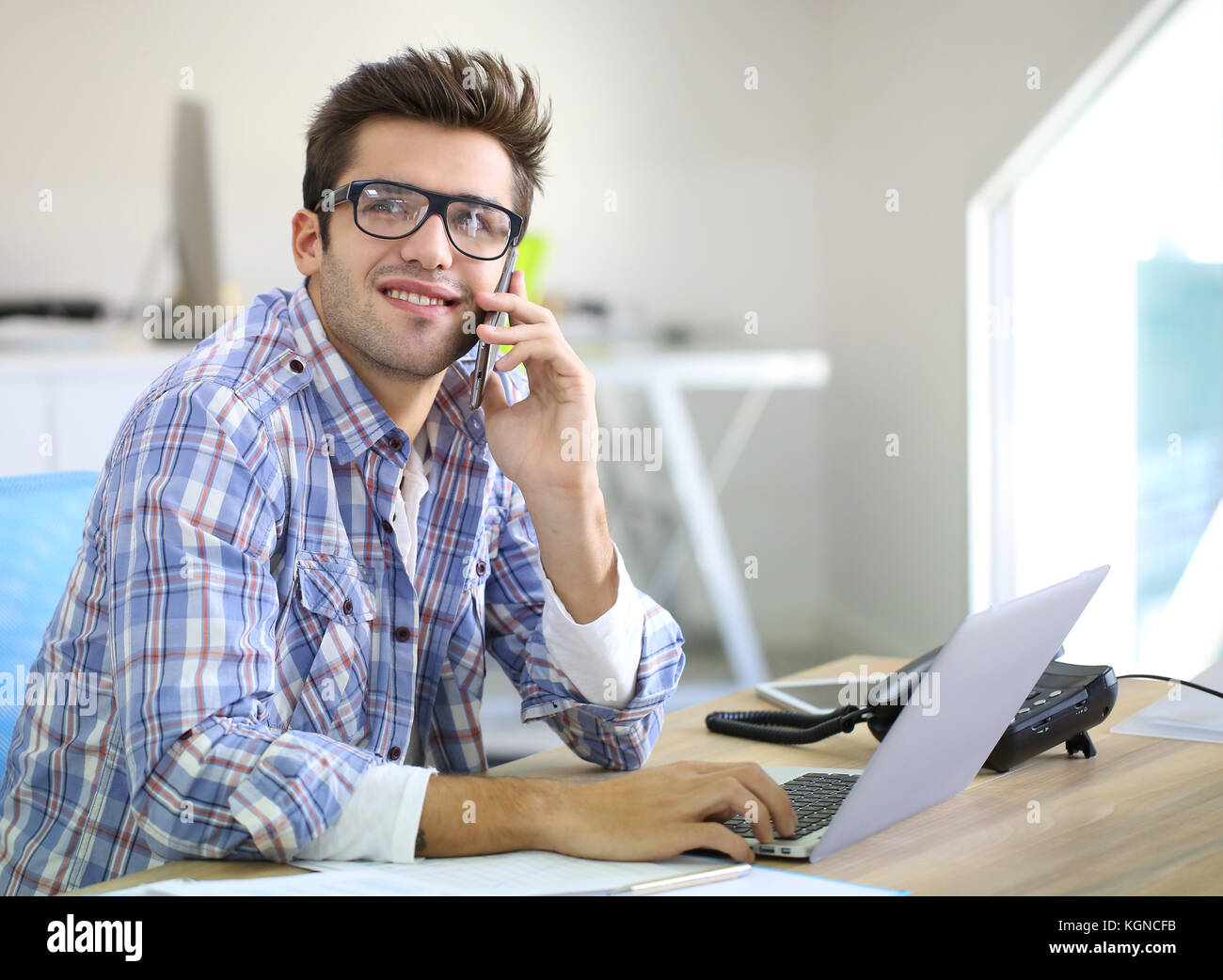 Trainee in office talking on the phone - Stock Image