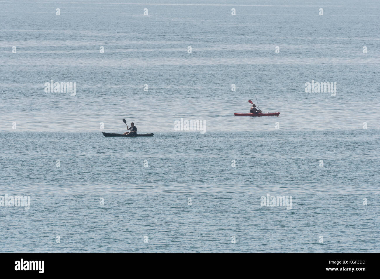 Two sea anglers paddling sea kayaks silhouetted against the water. Line fishing for mackerel and similar in shallow - Stock Image