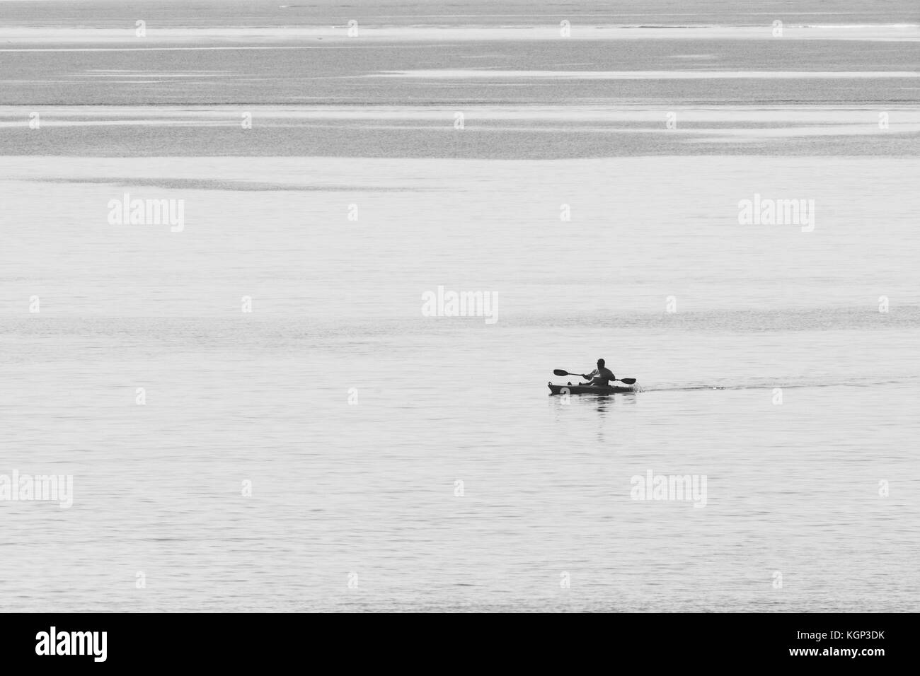 Black & white image of sea angler in sea kayak silhouetted against water. Line fishing for mackerel and similar - Stock Image