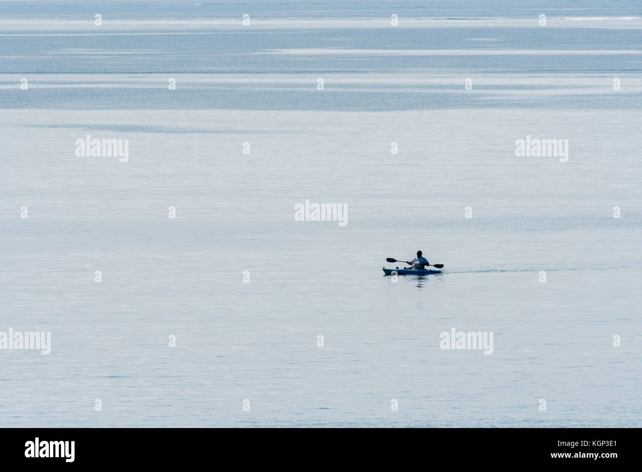 Lone sea angler paddling sea kayak silhouetted against the water. Line fishing for mackerel and similar in shallow - Stock Image