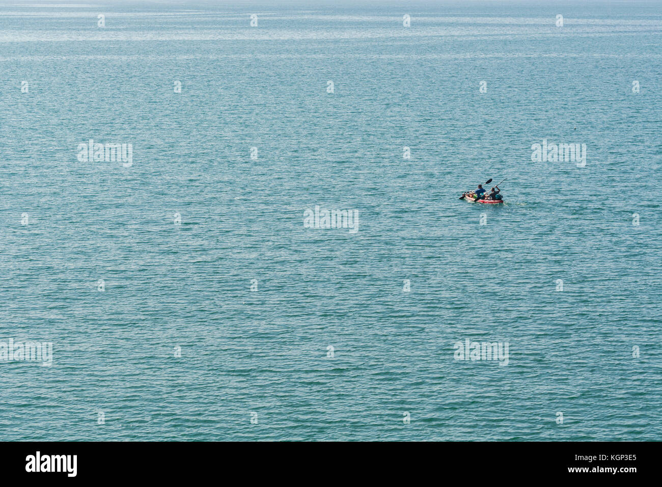 Twin seat sea kayak being paddled out to sea by two canoeists. They are heading out to line-fish for mackerel in - Stock Image