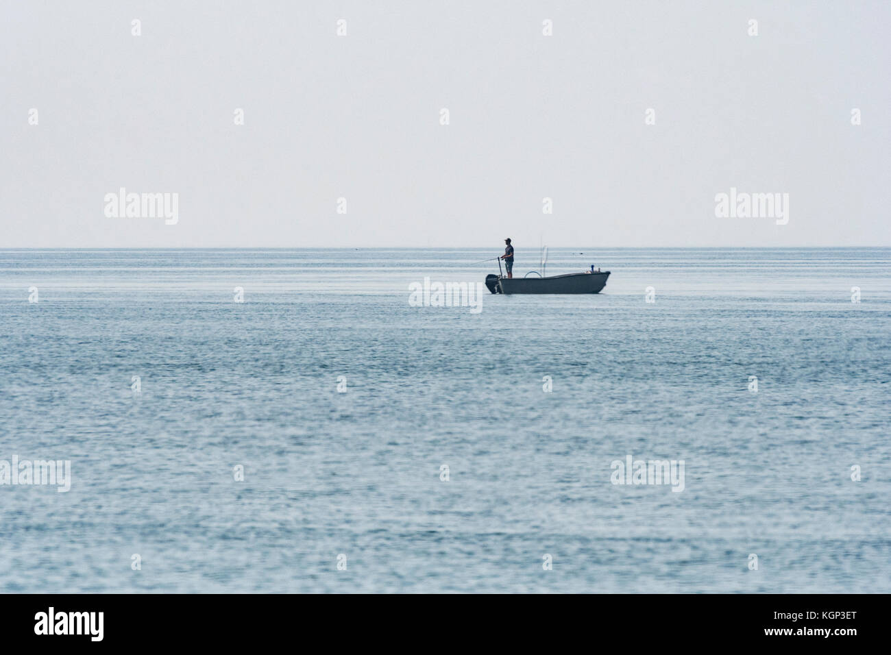 Distant shot of silhouette of lone fisherman handlining from the back of a small boat in Cornwall. Possible allegory - Stock Image