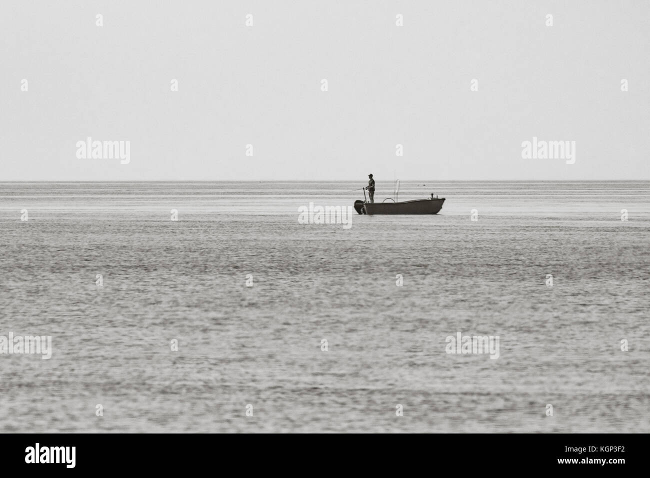 Distant black and white shot of silhouette of lone fisherman handlining from the back of a small boat in Cornwall. - Stock Image