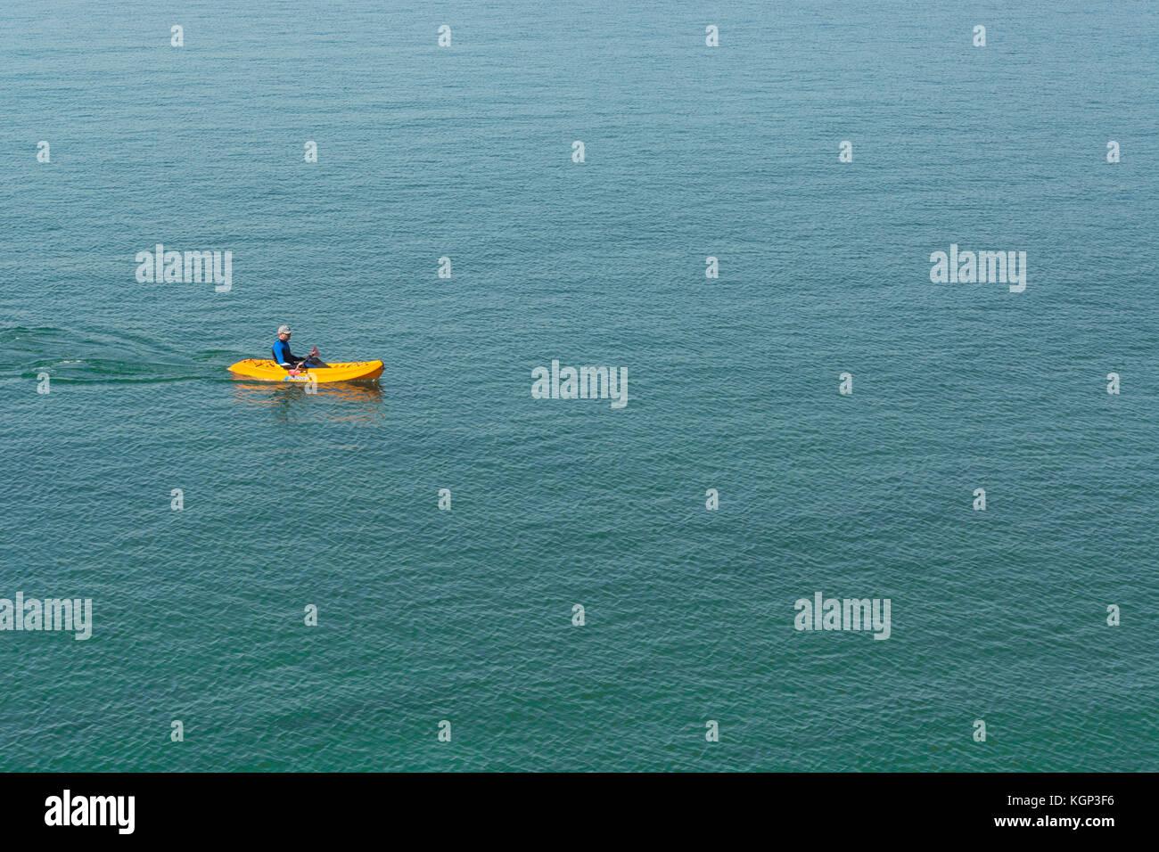 Canoeist paddling a yellow sea kayak in Cornwall. - Stock Image