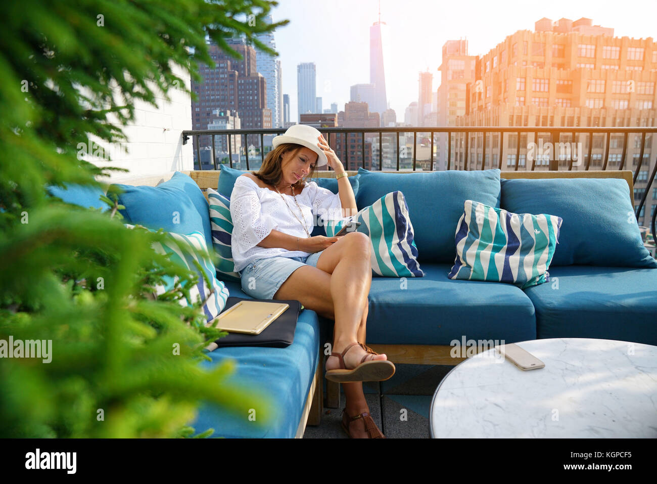 Woman relaxing in sofa on rooftop, NYC - Stock Image