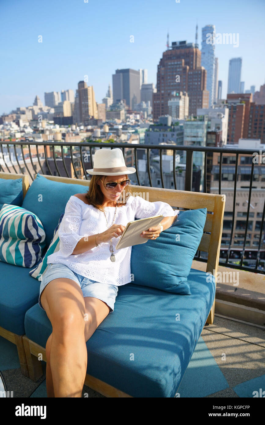 Woman on rooftop connected with tablet, NYC skyline in background - Stock Image