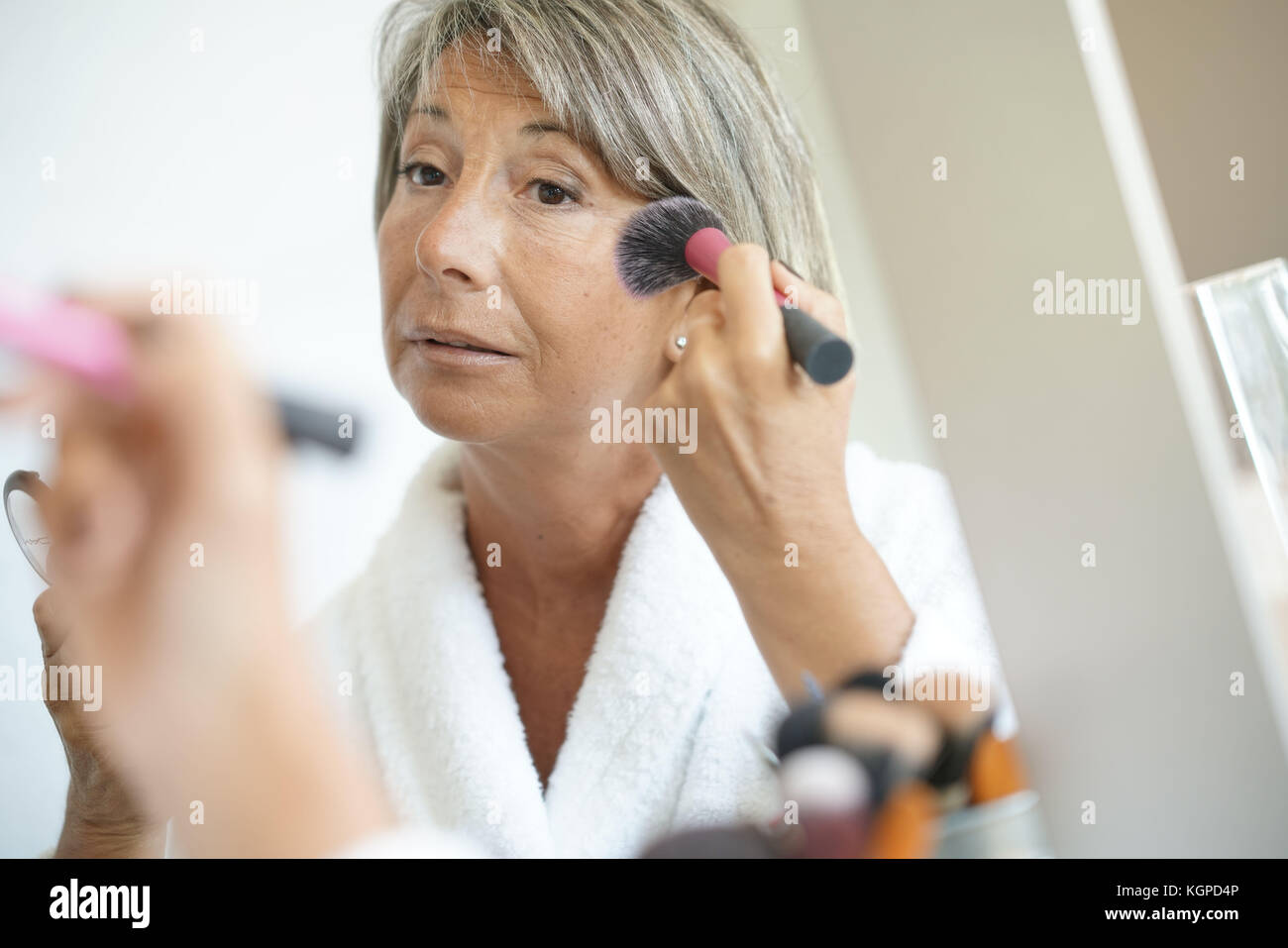 Senior woman in front of mirror putting makeup on - Stock Image