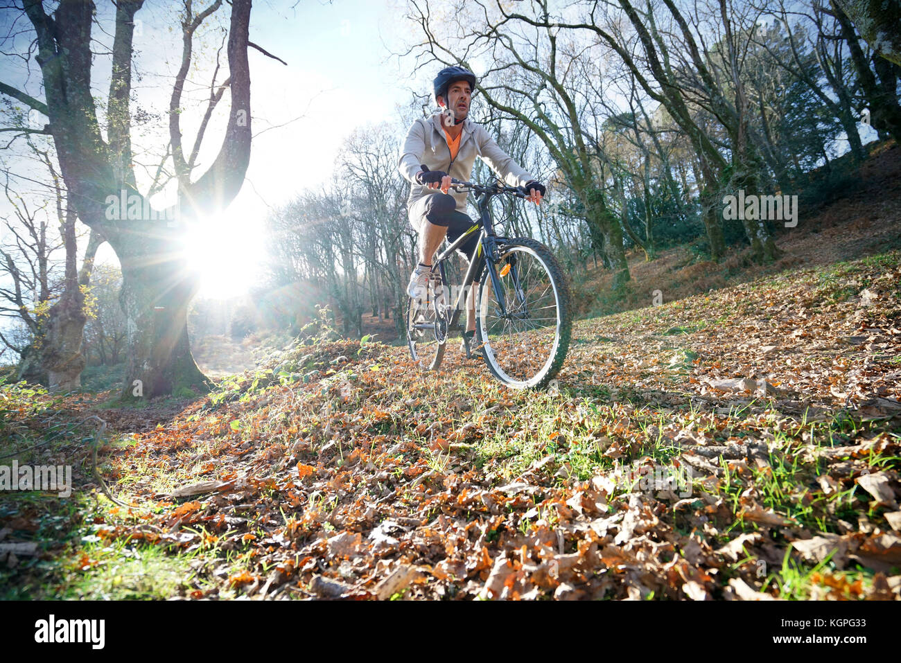 Mature man riding bike in the mountain - Stock Image