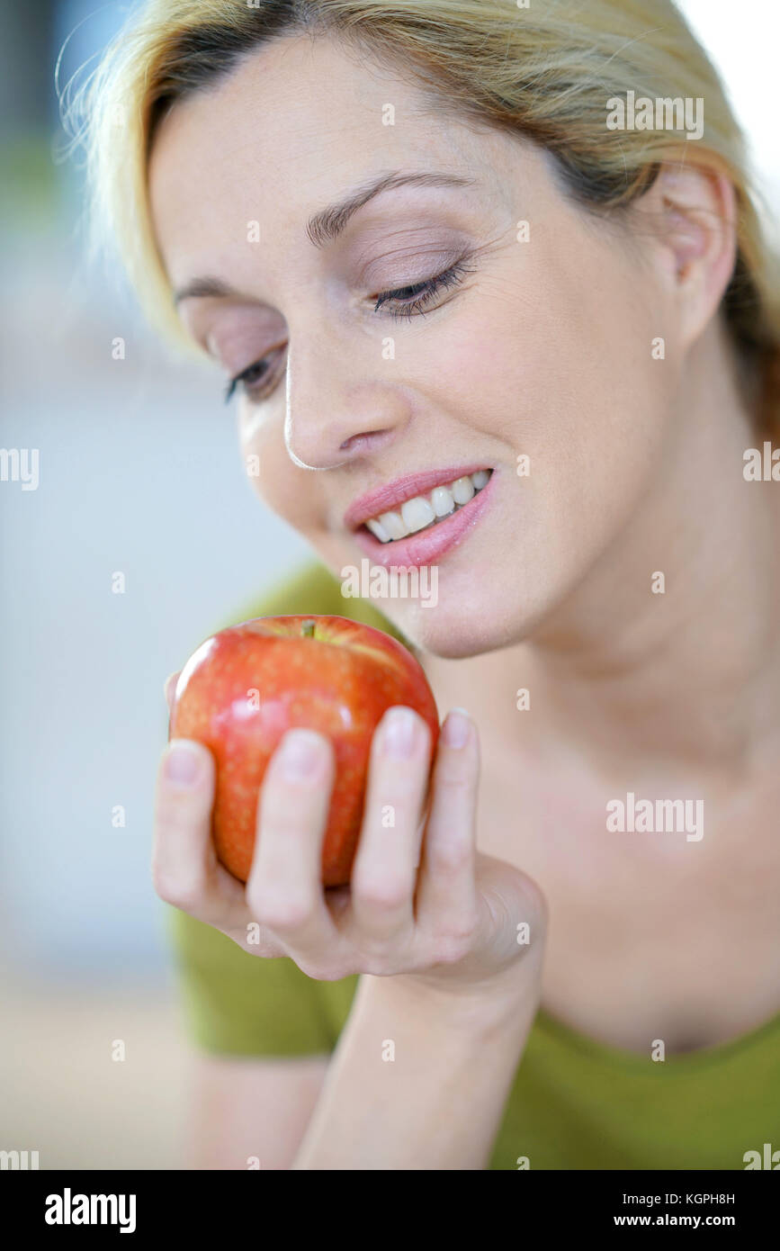 Portrait of blond woman eating an apple - Stock Image