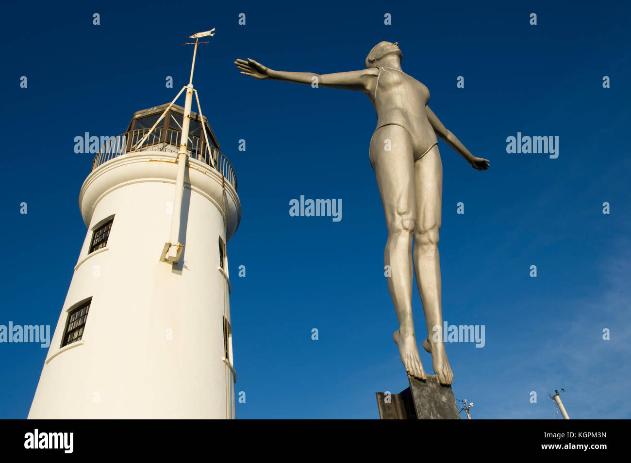 The Diving Belle statue and lighthouse located on the harbour in the North Yorkshire seaside town of Scarborough - Stock Image
