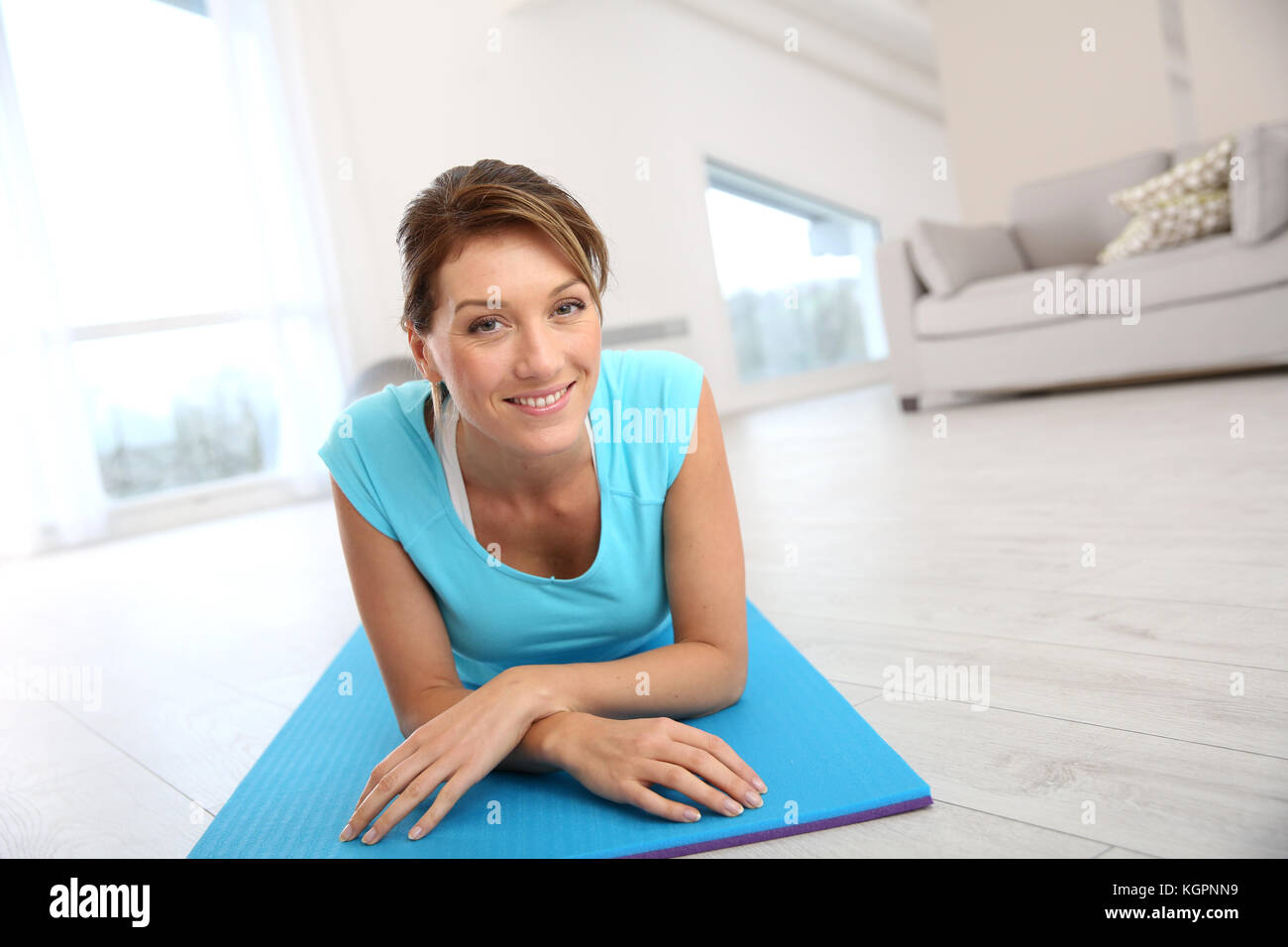 Beautiful fitness woman laying in gym floor - Stock Image