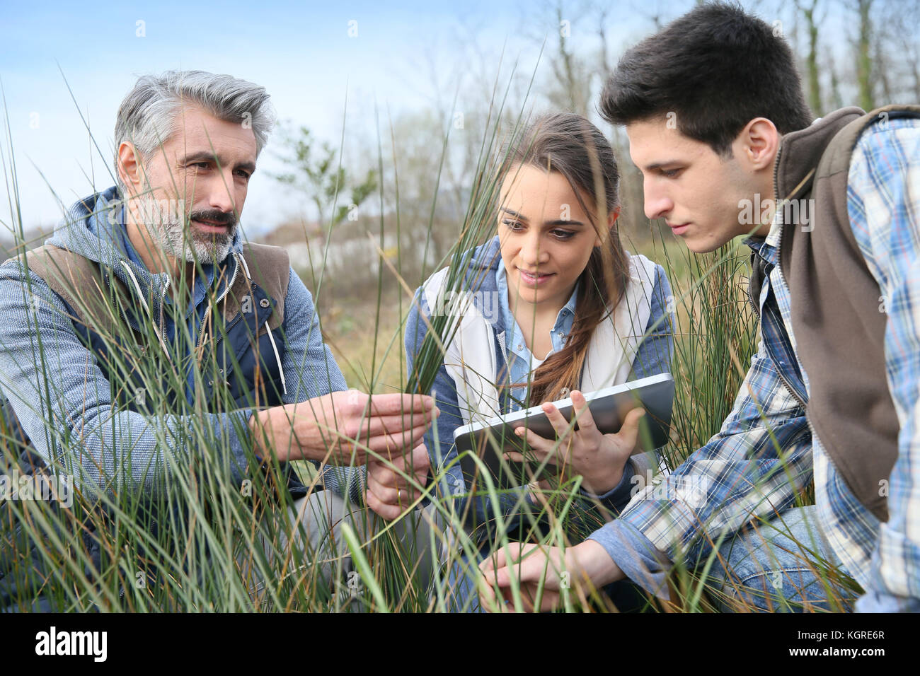 Teacher with students in agronomy looking at vegetation - Stock Image