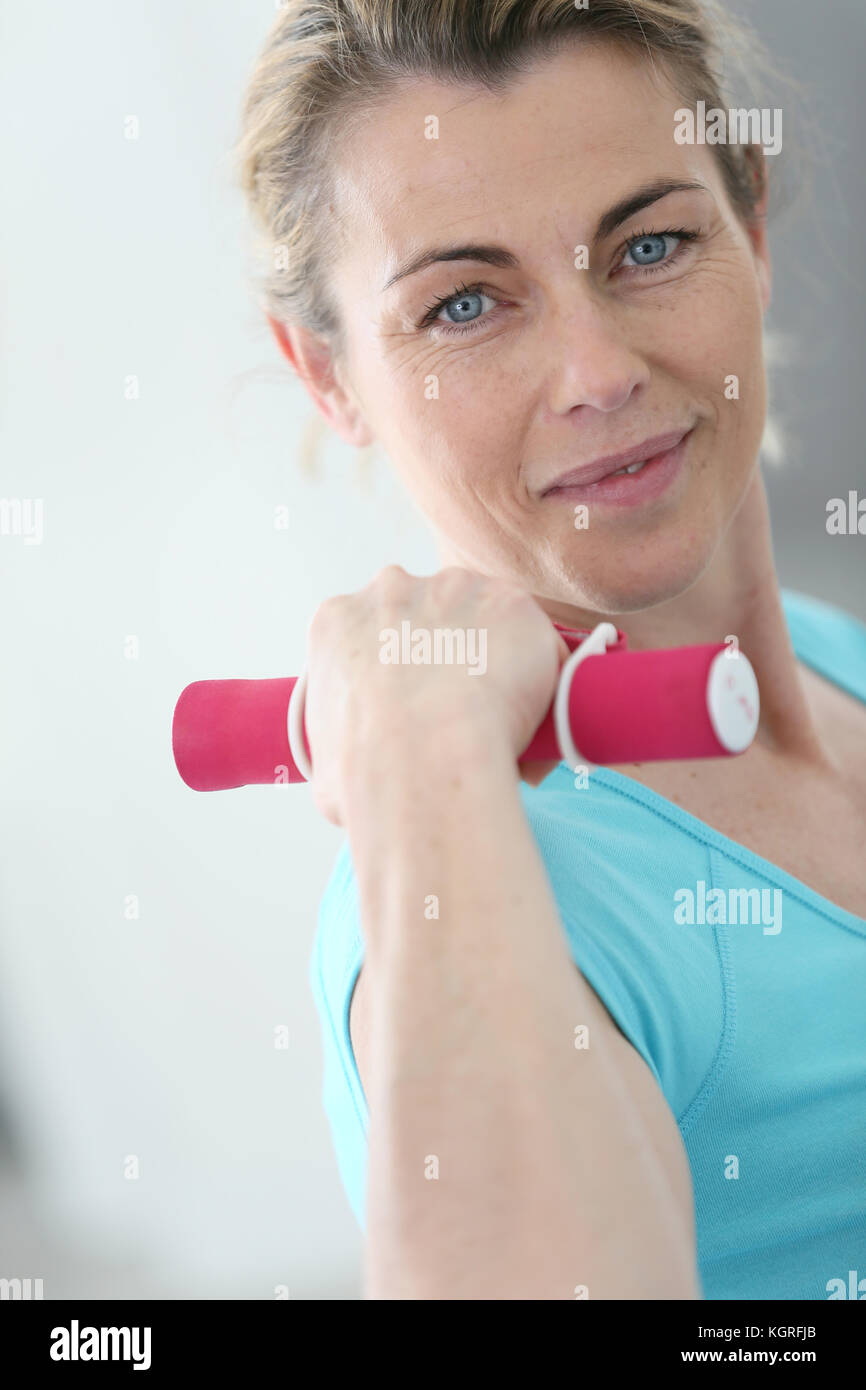 Portrait of mature fitness woman lifting dumbbells - Stock Image