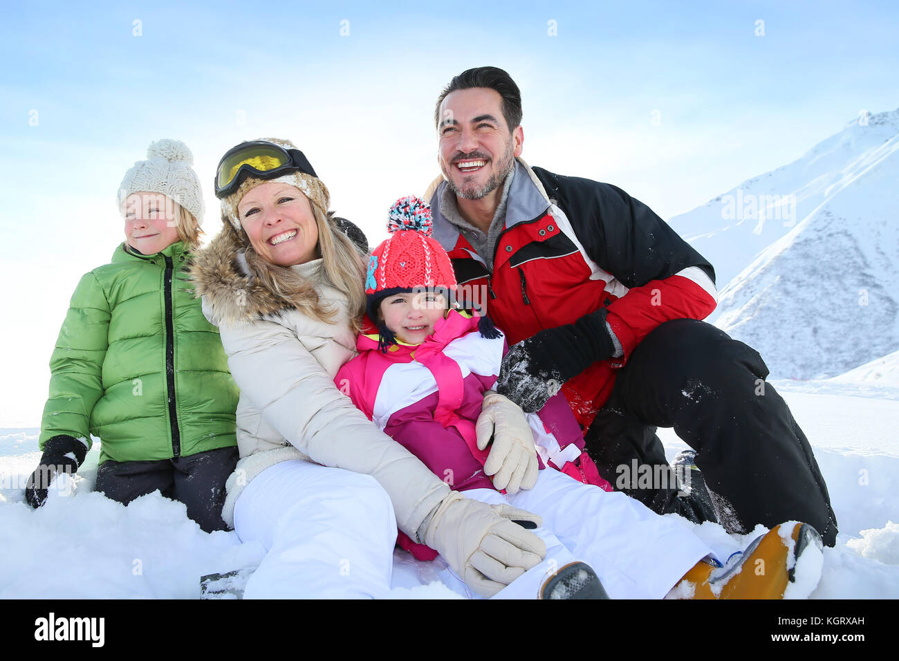 Cheerful family sitting in snow - Stock Image