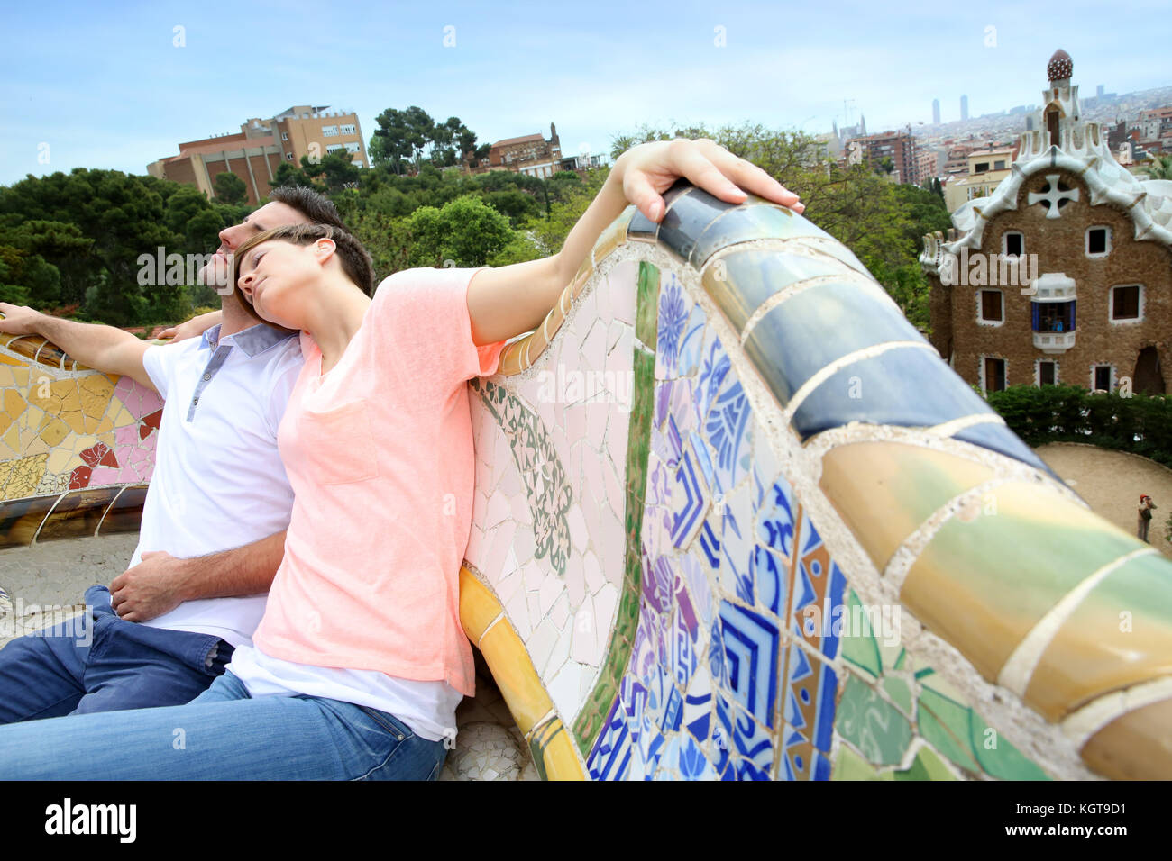 Couple of tourists relaxing on Guell Park bench - Stock Image