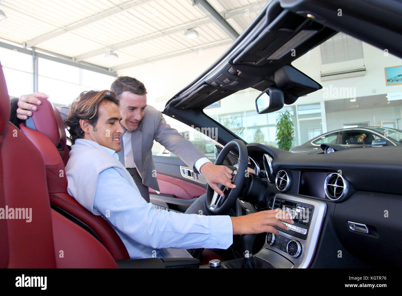 Car seller showing interior details to purchaser - Stock Image