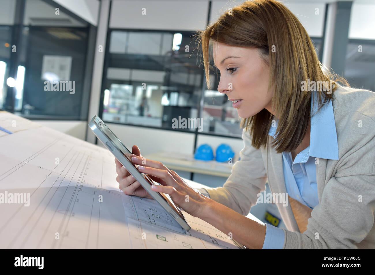 Woman engineer working on digital tablet - Stock Image