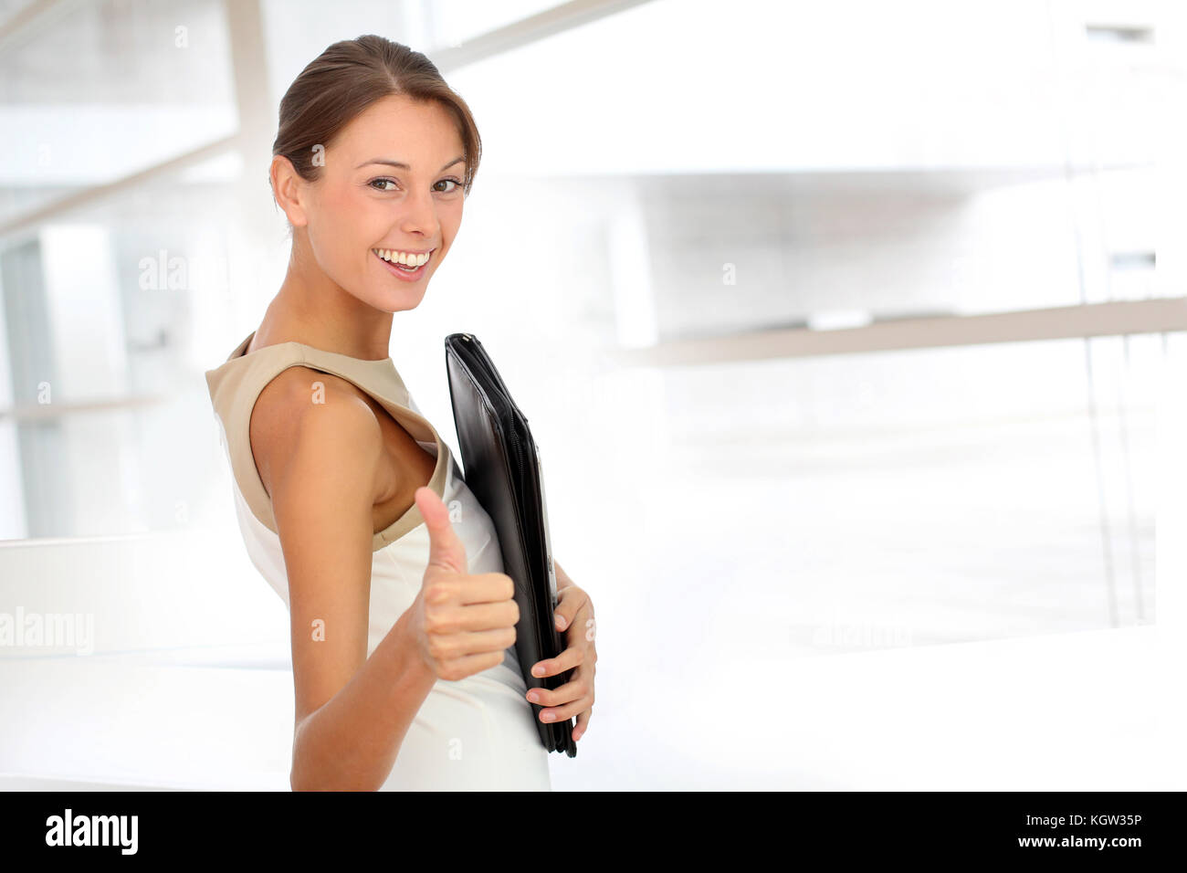 Cheerful businesswoman showing thumb up - Stock Image