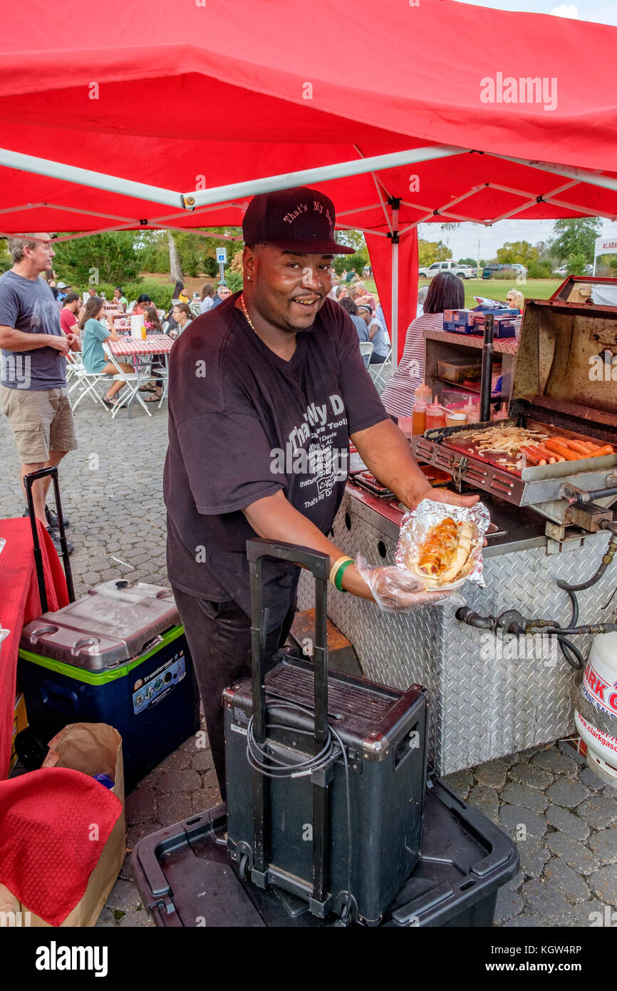 Proud hotdog vendor holding a large hotdog with all the extras at a community street fair showing his delicious - Stock Image
