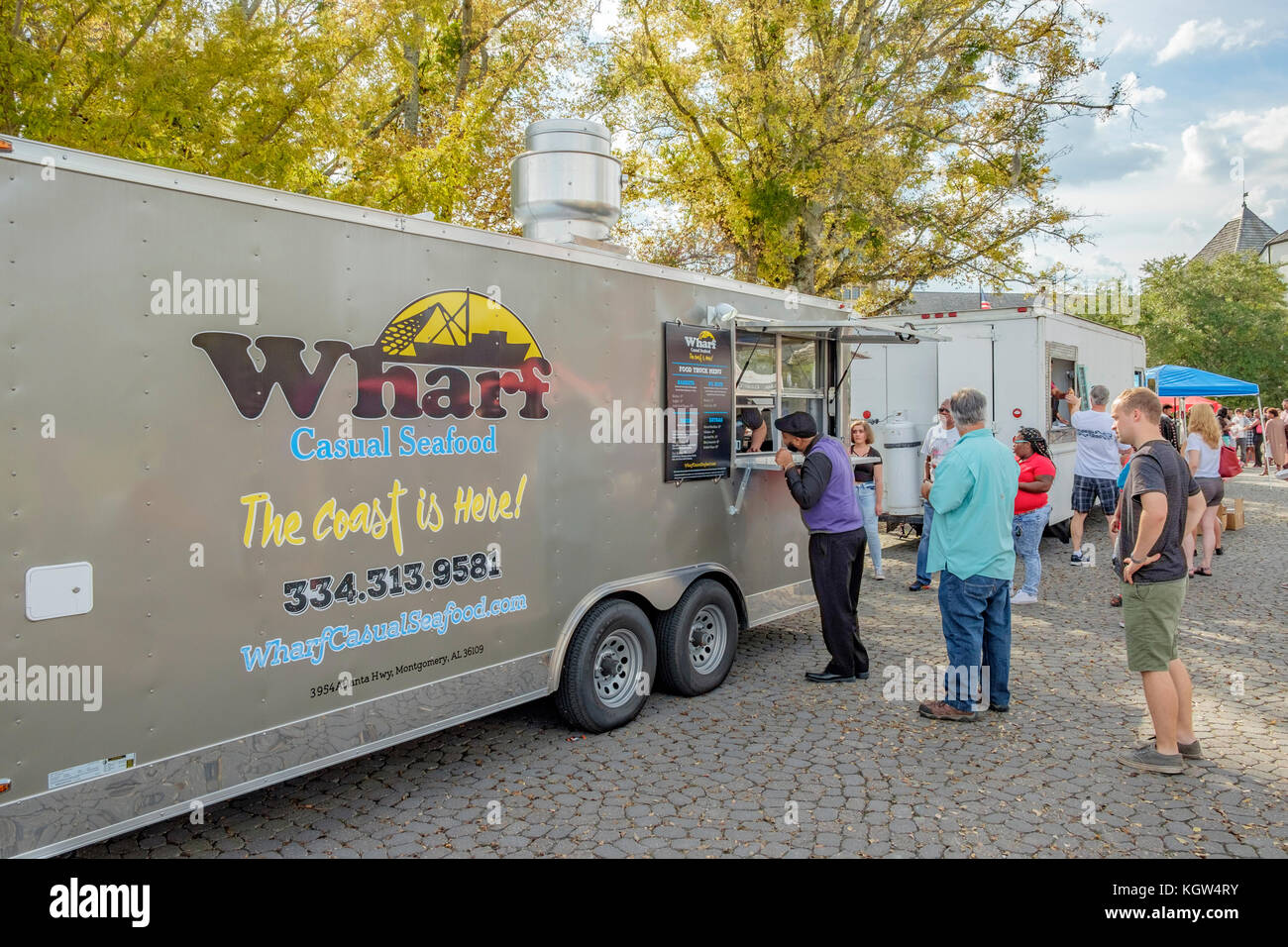 Customers at a food truck festival in a small community in Montgomery Alabama, USA, wait in line, or queue, to order - Stock Image