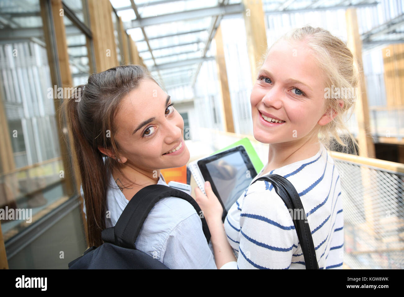 Cheerful teenage girls using tablet at school - Stock Image