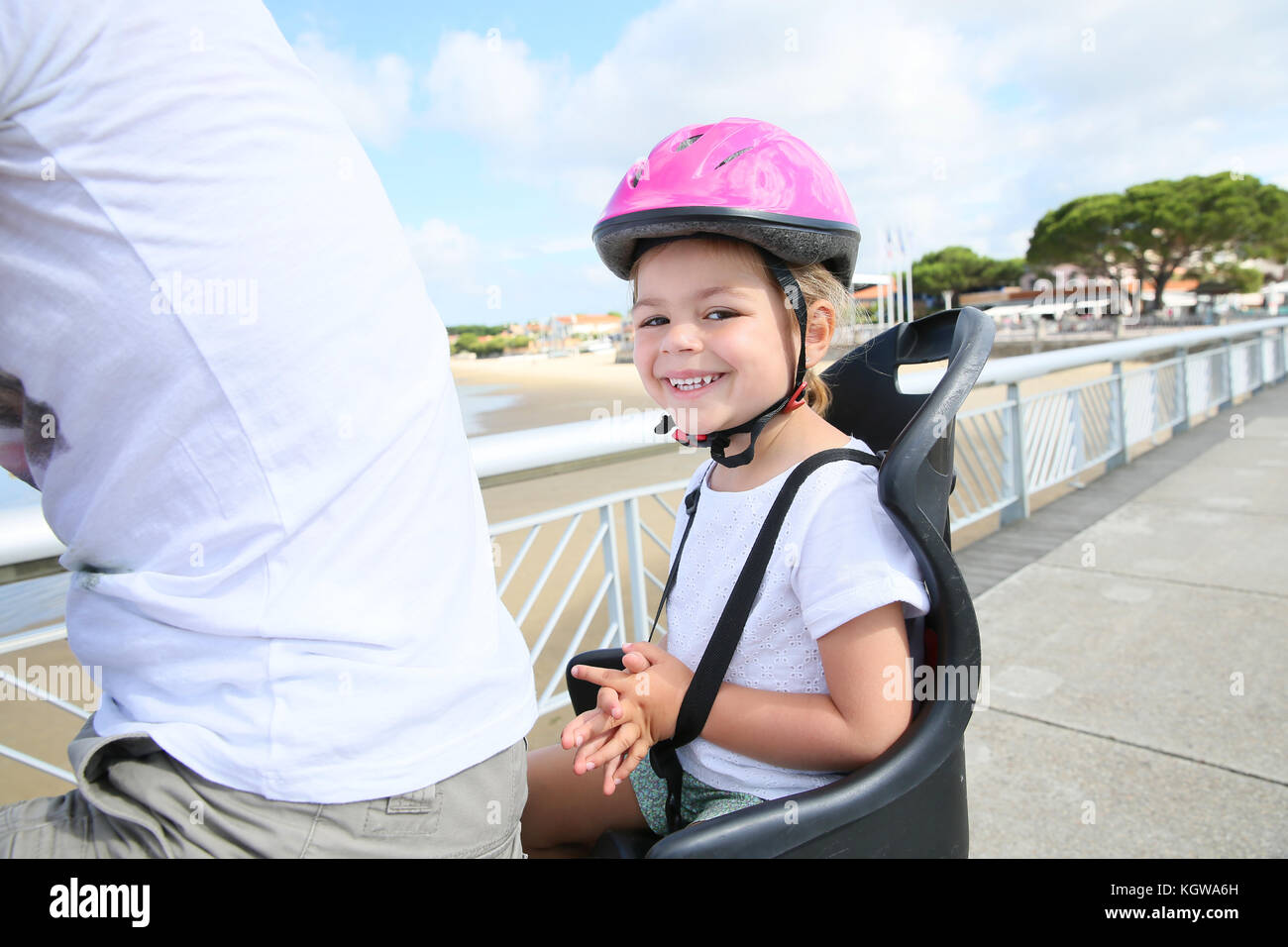 Smiling little girl sitting in child seat on bicycle - Stock Image