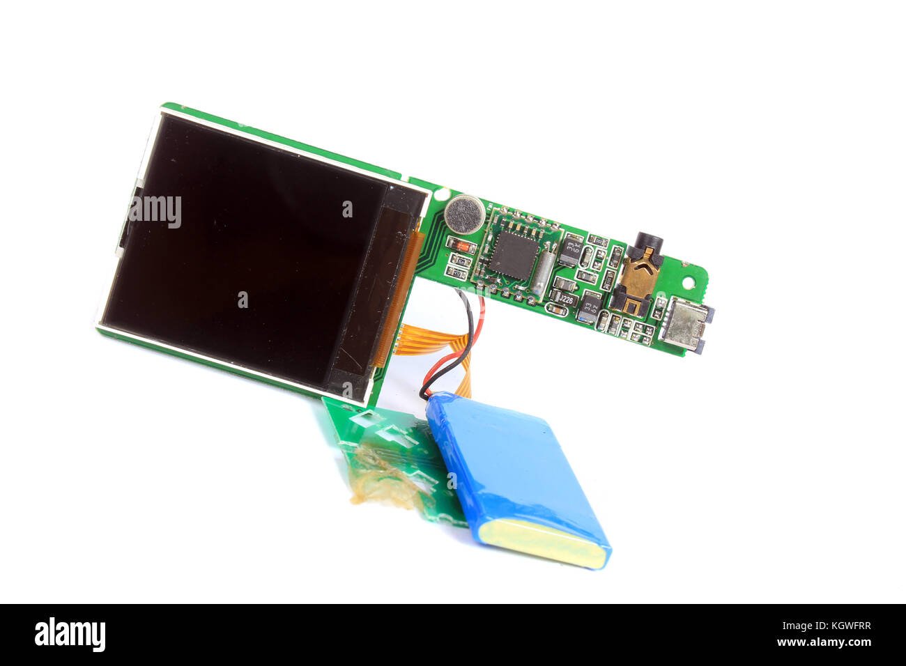 An old MP3 player stripped down showing its components like circuit board, battery and lcd screen. - Stock Image