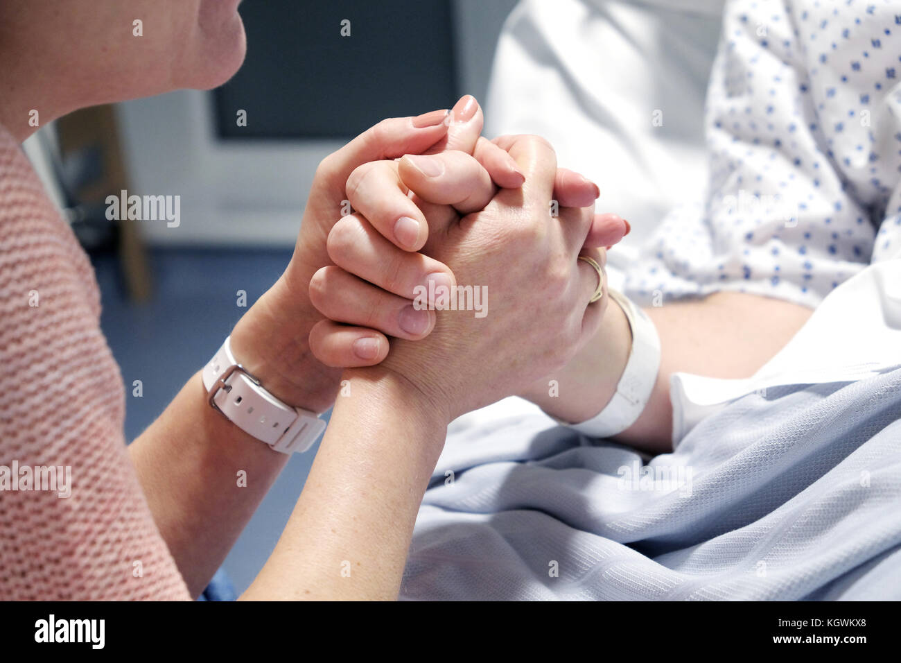 A mother clasps the hand of her son who is lying ill in a hospital bed. Offering support as he starts his recovery, - Stock Image