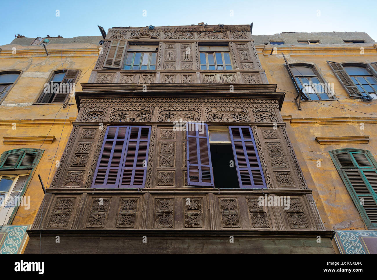 Facade of an old residential building with wooden ornate engraved wall, yellow painted wall, and violet painted - Stock Image