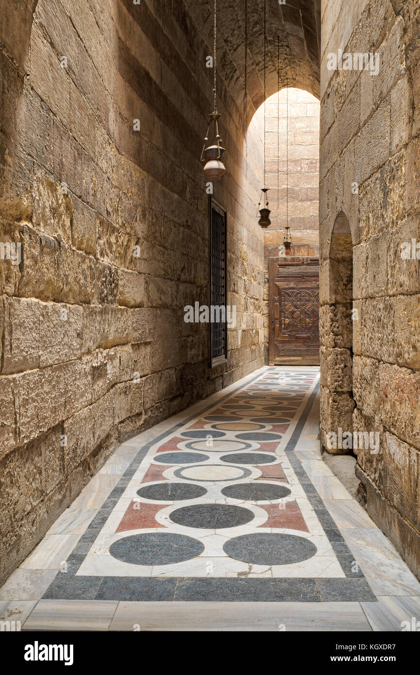 Arched corridor leading to the courtyard of Sultan Barquq mosque with stone bricks wall, ornate colored marble floor - Stock Image