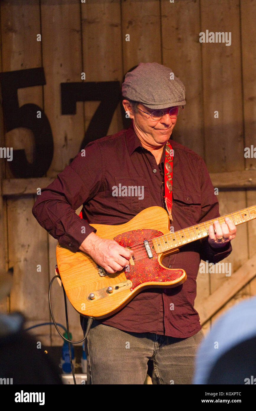 Man in hat plays a Fender Telecaster at the Maverick festival - Stock Image