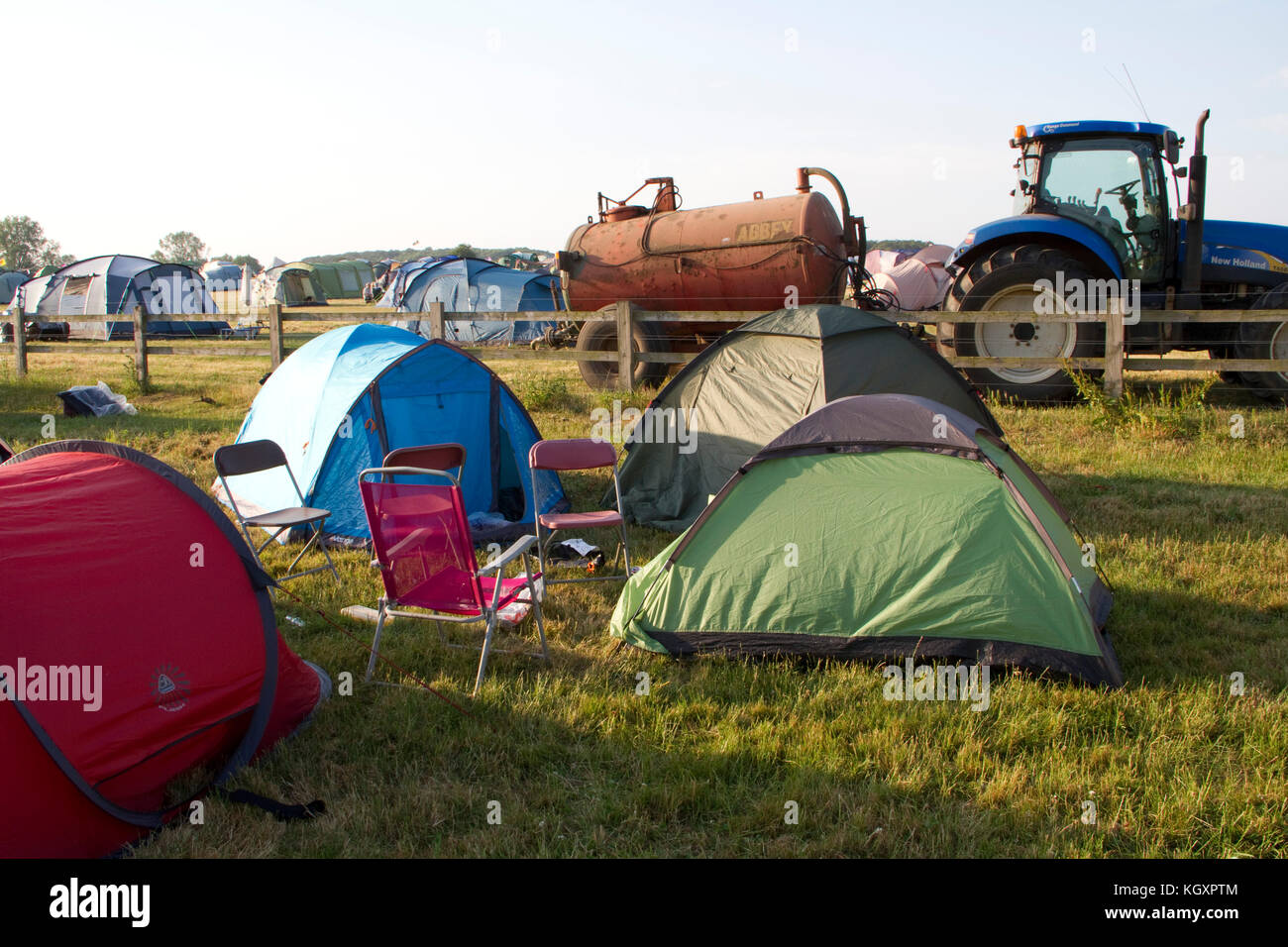 Tents at a music festival with a tractor and tanker in the background - Stock Image