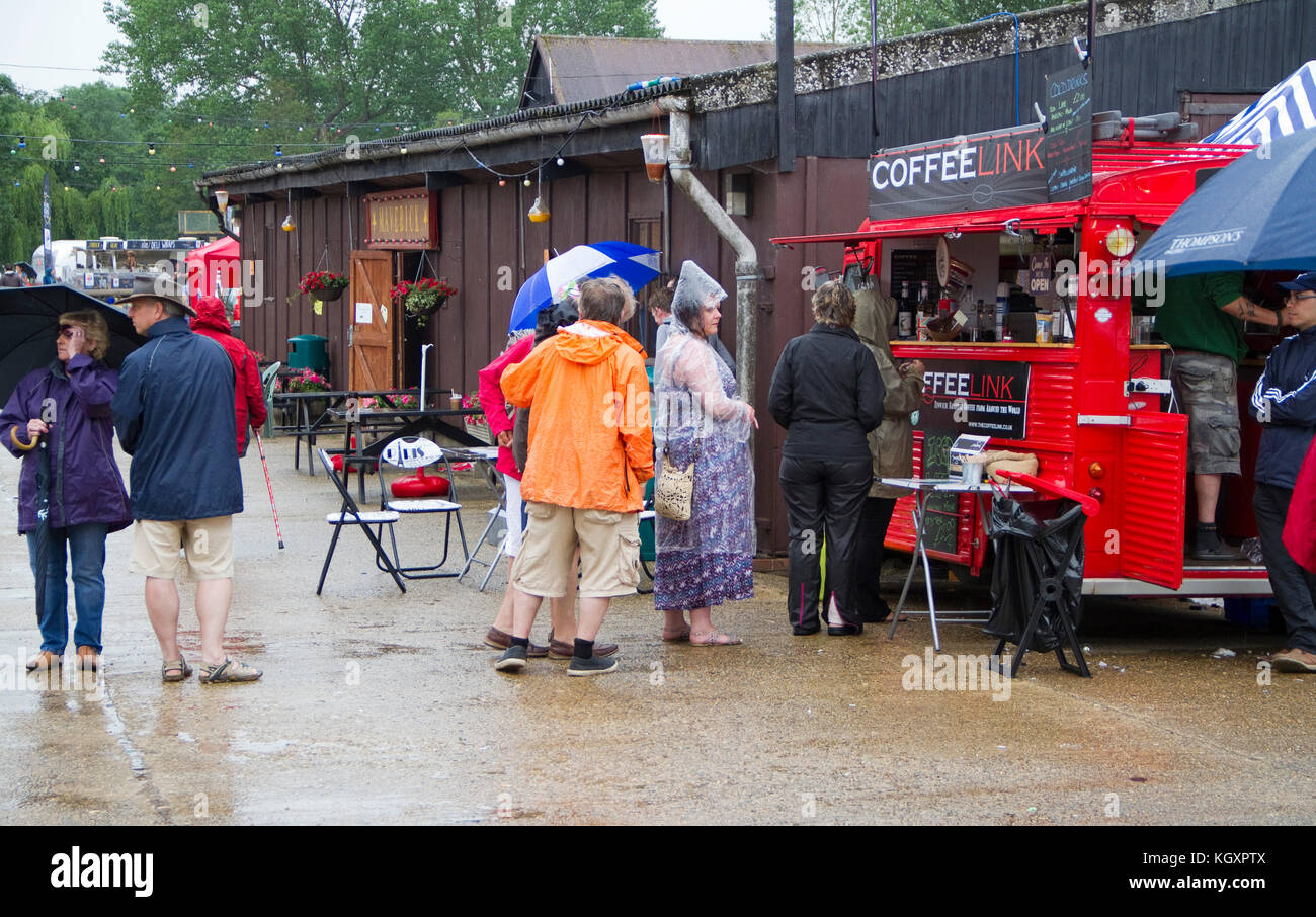 Festival goers queue in the rain for  coffee van - Stock Image