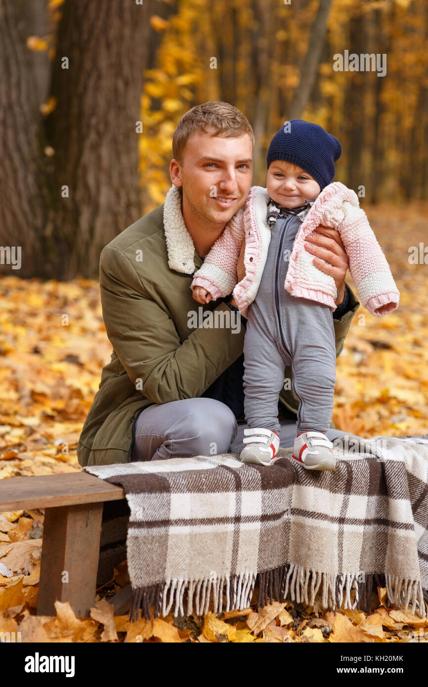 young father with a little daughter in autumn park. Happy family, paternal love, autumn season, outdoors concept - Stock Image