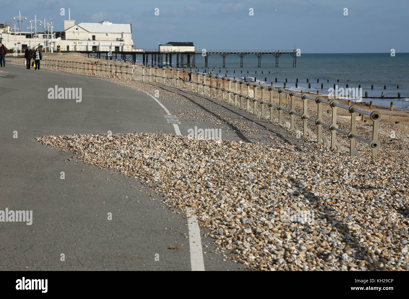 shingle overflows onto the seafront promenade in Bognor Regis, Sussex, UK, following stormy winter weather. Shows - Stock Image