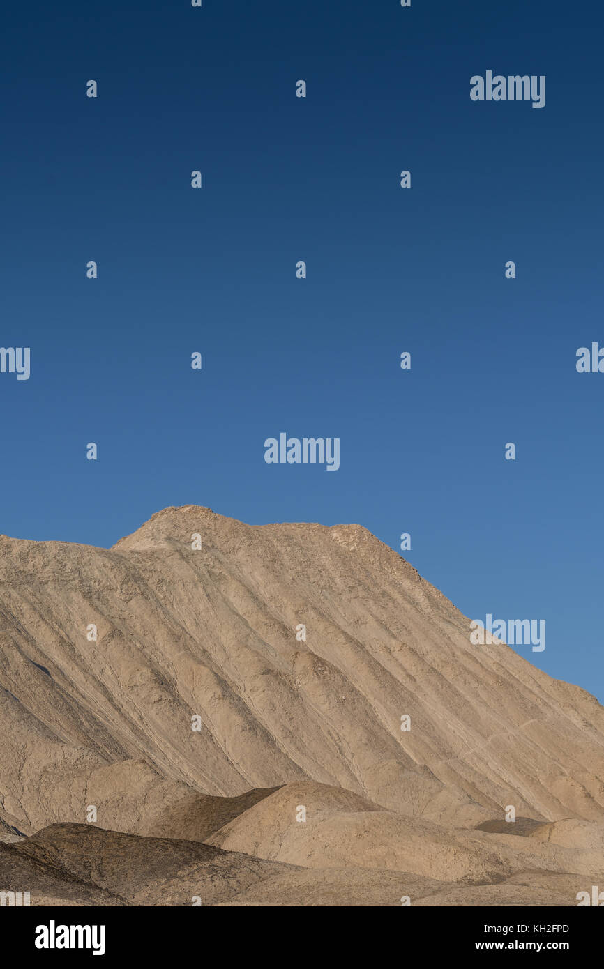 Blue Sky Over Tan Desert Hill in Death Valley wilderness - Stock Image