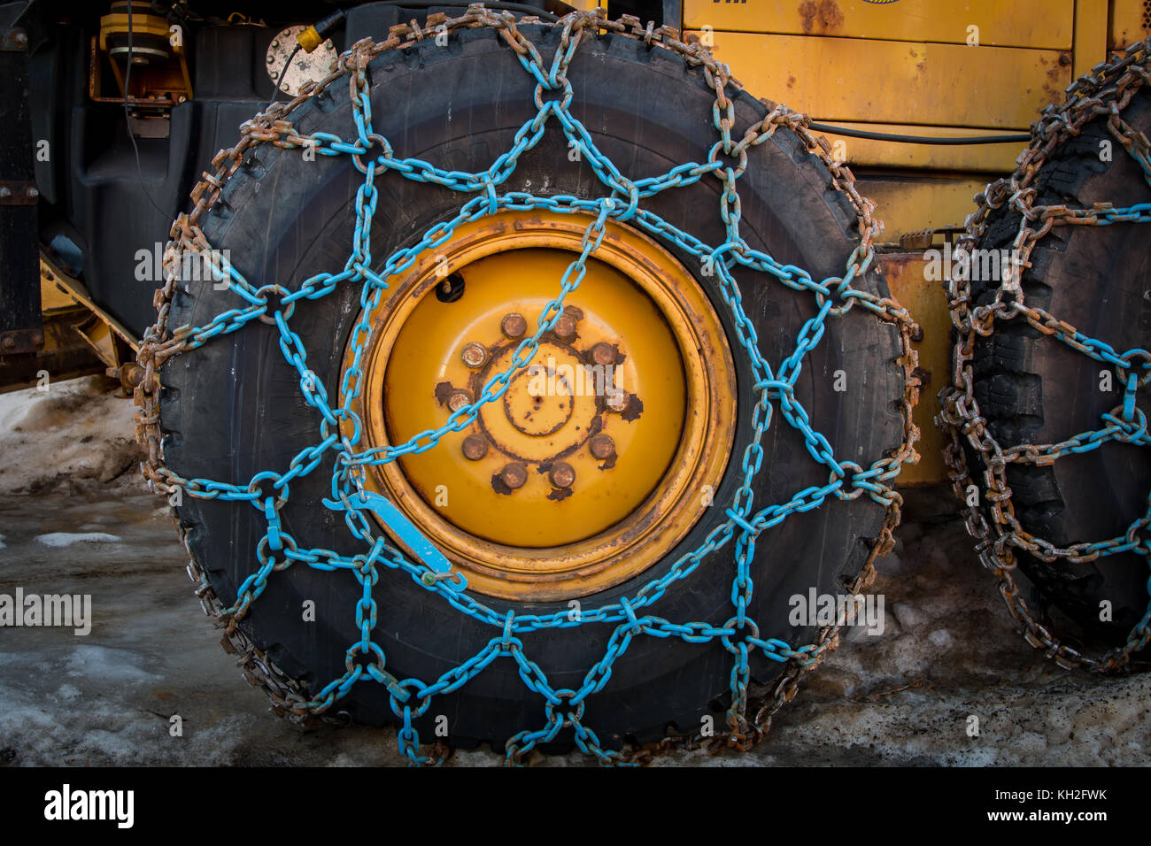 Blue Snow Chains wrapped around plow tire - Stock Image