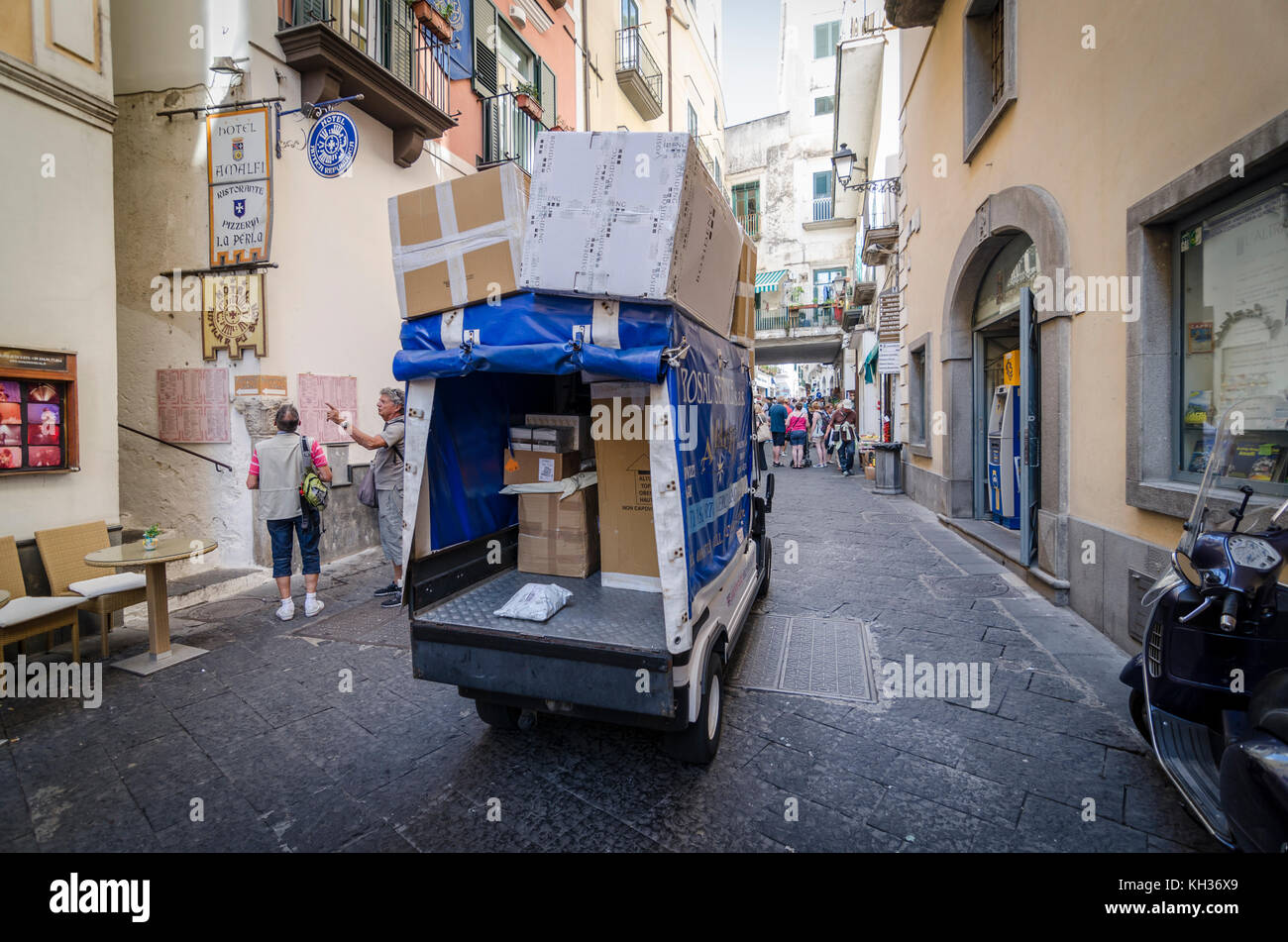 Small electric vehicle EV delivering parcels through the narrow historic streets in the town of Amalfi in Italy - Stock Image