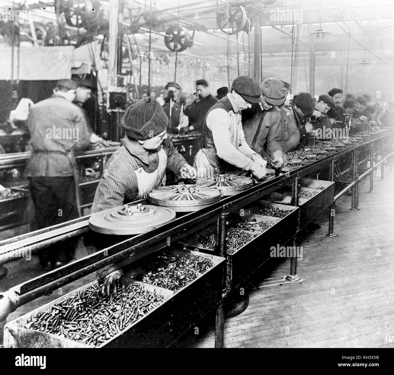Workers on the first moving assembly line put together magnetos and flywheels for Ford autos, Ford assembly line - Stock Image