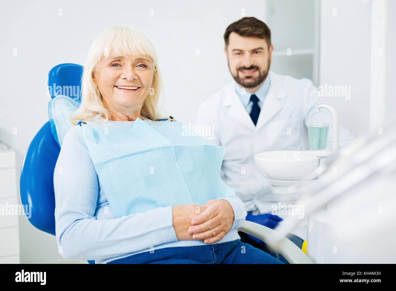 Pleased woman sitting on dental chair - Stock Image