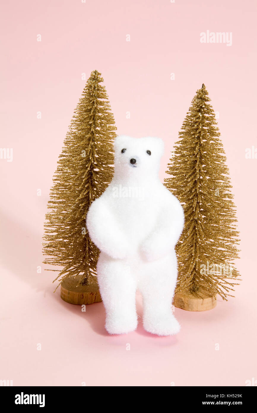 isolated christmas gold trees with white polar bear next to it on a vibrant pink background. Minimal still life - Stock Image