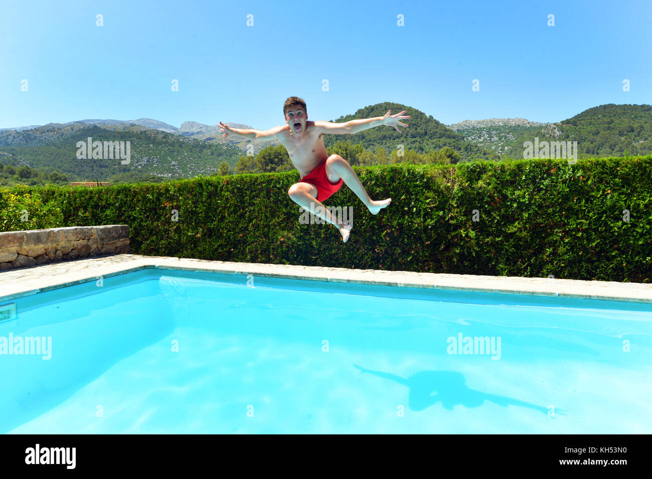 Teenage boy jumping into a private villa swimming pool - Stock Image