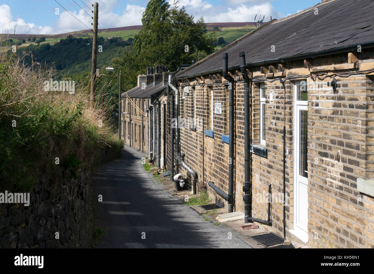 Row of old stone cottages on narrow road, Luddenden Foot, West Yorkshire - Stock Image