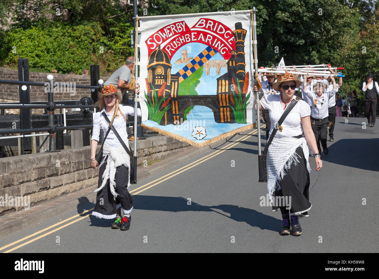 2017 Sowerby Bridge Rushbearing Festival procession with women carrying banner, West Yorkshire - Stock Image