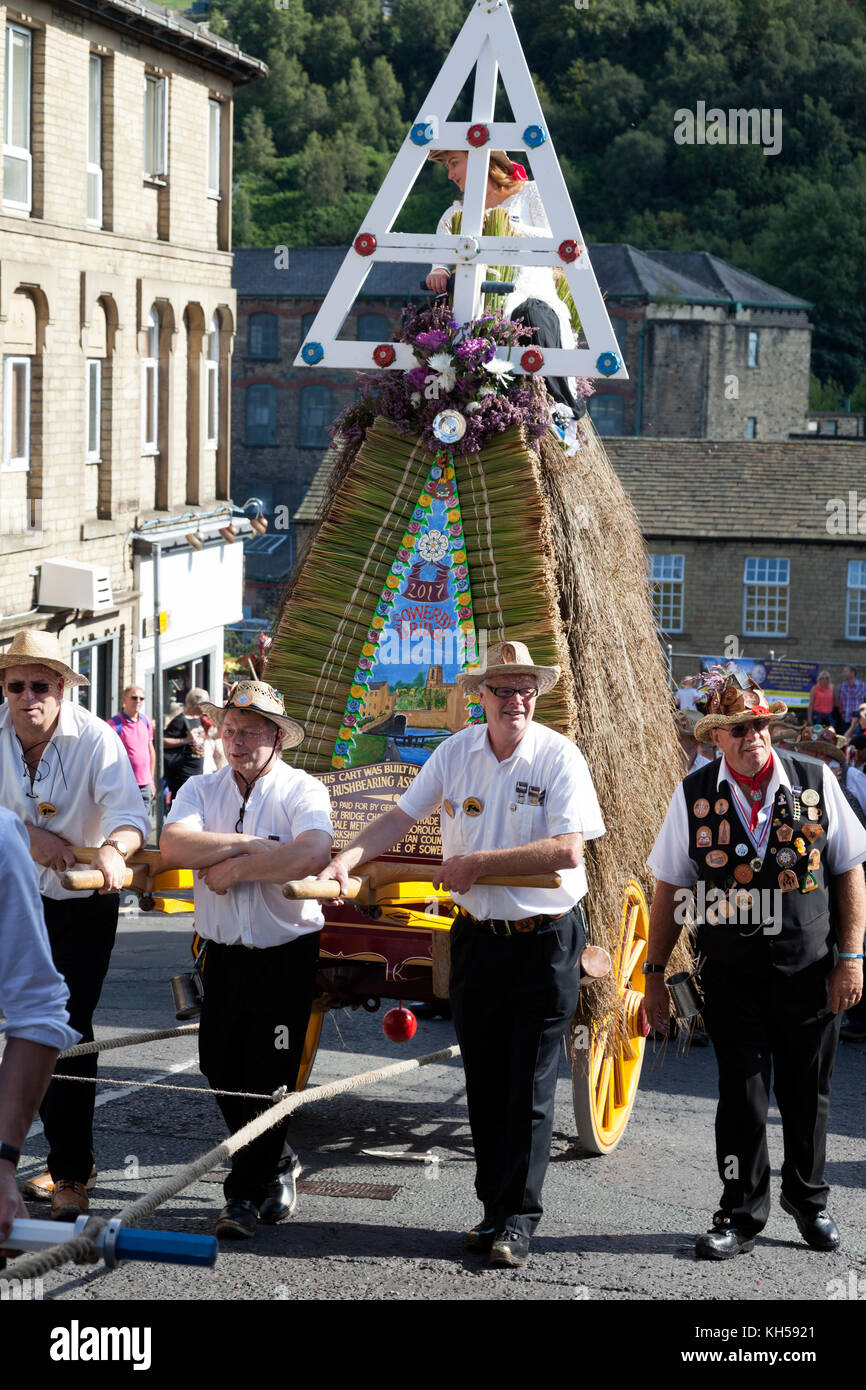 Men pulling the rushcart at the Sowerby Bridge Rushbearing Festival 2017 - Stock Image