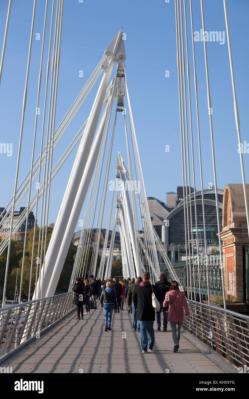 People walking across the Golden Jubilee Bridge, London - Stock Image
